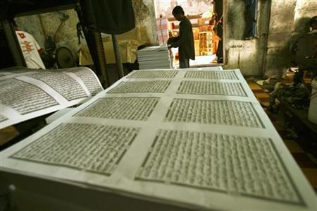 A worker looks checks printing paper for the Koran near the Sunan Ampel mosque in Surabaya, Indonesia East Java province, July 27, 2011. The demand for the Koran usually increase from 10 thousand to 20 thousand books ahead of the month of Ramadan, according to Suyanto, the owner of the printing press. REUTERS/Yusuf Ahmad