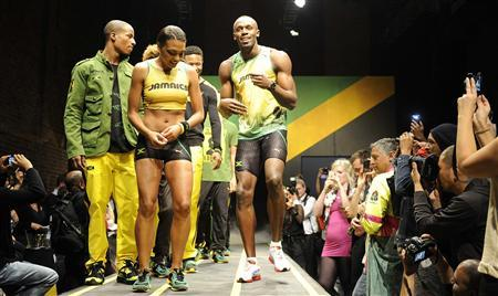 Jamaican sprinter Usain Bolt (R) models the Jamaican team's kit for the London 2012 Olympic Games, designed by Cedella Marley, at a fashion show in London June 1, 2012. REUTERS/Paul Hackett