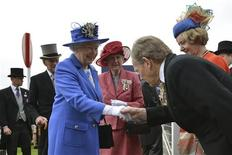 Britain's Queen Elizabeth shakes hands with a racegoer as she arrives with Prince Philip (2nd L)at the Epsom Derby festival in Epsom, southwest of London June 2, 2012. Queen Elizabeth gets four days of celebrations to mark her 60 years on the British throne under way on Saturday with one of her favourite pastimes, a trip to the horse races, as tributes to the long-serving monarch pour in. REUTERS/Ben Stansall/pool