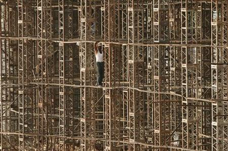 A construction worker stands on scaffolding at the construction site of a bridge on the outskirts of Jammu May 31, 2012. REUTERS/Mukesh Gupta