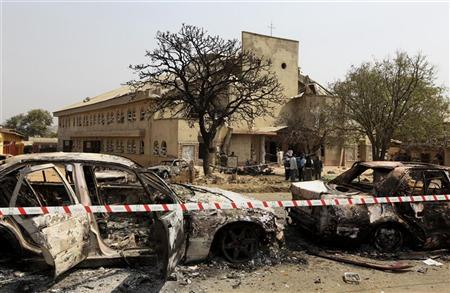 A security barrier marks the scene of a car bomb explosion at St. Theresa Catholic Church (background) at Madalla, Suleja, just outside Nigeria's capital Abuja, December 25, 2011. REUTERS/Afolabi Sotunde