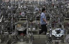 A worker walks past machines on a photo and mirror frame assembly line at a factory in Zibo, Shandong Province May 28, 2012. REUTERS/Aly Song