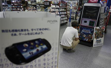 A man plays a Nintendo 3DS portable game console near a advertisement of Sony's PlayStation Vita handheld gaming device at a Yamada Denki electronics retail store in Tokyo June 4, 2012. REUTERS/Toru Hanai