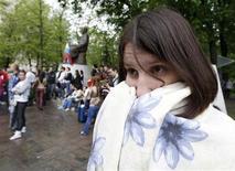 Женщина кутается в плед во время демонстрации в Москве, 8 мая 2012 года. Ненастная погода не торопится уходить из российской столицы - синоптики ожидают очередную прохладную и дождливую неделю. REUTERS/Sergei Karpukhin