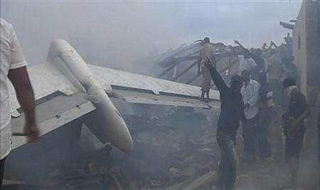 A still image taken from video shows emergency workers and volunteers around the wreckage of the tail of a plane that crashed in Lagos June 3, 2012. REUTERS/Stringer