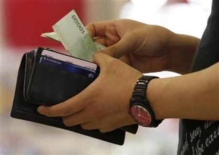 A customer takes money out of his wallet at a supermarket counter in Seoul June 8, 2011. REUTERS/Truth Leem
