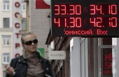 Женщина проходит мимо обменного пункта в Москве, 1 июня 2012 года. Рубль падает в начале торгов понедельника вслед за нефтяными котировками и на фоне глобального бегства от риска, вызванного долговым кризисом в еврозоне и угрозой замедления экономического роста в США. REUTERS/Sergei Karpukhin