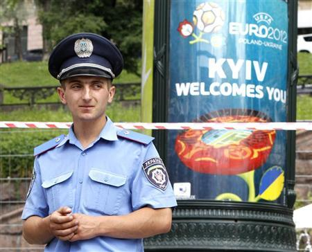 A policeman stands guard while a bomb expert inspects a suspicious-looking plastic bag in central Kiev that turned out to be harmless June 1, 2012. REUTERS/Gleb Garanich