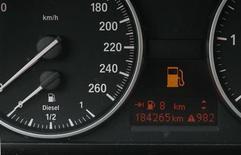 Датчик бензина на приборной панели автомобиля в Бохуме, 5 апреля 2012 года. Цены на нефть продолжают снижаться после выхода слабой экономической статистики Китая и США на прошлой неделе. REUTERS/Wolfgang Rattay