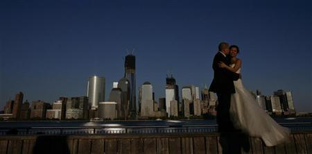 A couple, posing for their pre-wedding photographs, are back-dropped by the One World Trade Center and Manhattan skyline as seen from New Jersey April 29, 2012. REUTERS/Eduardo Munoz