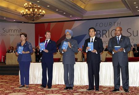 (From L-R) Brazil's President Dilma Rousseff, Russian President Dmitry Medvedev, Indian Prime Minister Manmohan Singh, Chinese President Hu Jintao and South African President Jacob Zuma hold copies of the BRICS report after its release during a plenary session of the summit in New Delhi March 29, 2012. REUTERS/B Mathur