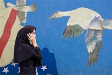 A woman talks on her mobile phone while passing a mural on a wall of the former U.S. embassy in Tehran November 5, 2008. REUTERS/Morteza Nikoubazl (IRAN)