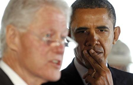 U.S. President Barack Obama listens to former U.S. President Bill Clinton speak about the economy during a tour of an energy-efficient office building renovation near the White House in Washington December 2, 2011. REUTERS/Kevin Lamarque