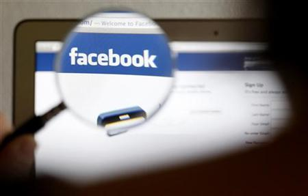 In this photo illustration, a Facebook logo on a computer screen is seen through a magnifying glass held by a woman in Bern May 19, 2012. Picture taken May 19, 2012. REUTERS/Thomas Hodel