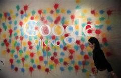 Женщина проходит мимо стены с логотипом Google в офисе интернет-компании в Чикаго, 20 марта 2012 года. Интернет-гигант Google Inc купит Meebo Inc, новый сервис, помогающий веб-издателям распространять свои сайты через социальные сети, сообщила Meebo в своем блоге. REUTERS/Jim Young