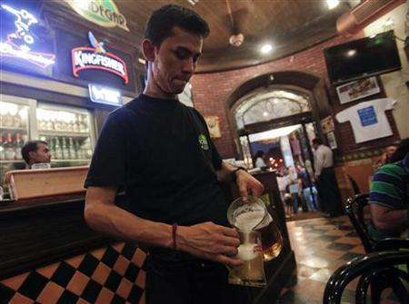 A waiter pours a mug of beer at a pub in Mumbai June 3, 2012. REUTERS/Vivek Prakash