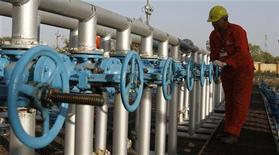 Рабочий проверяет оборудование на заводе Oil and Natural Gas Corp (ONGC) в Ахмадабаде, 2 марта 2012 года. Индийская государственная нефтегазовая компания Oil and Natural Gas Corp (ONGC) думает о приобретении у ConocoPhillips нефтеносных песков в Канаде за $5 миллиардов, сообщил Рейтер источник, непосредственно знакомый с ситуацией. REUTERS/Amit Dave