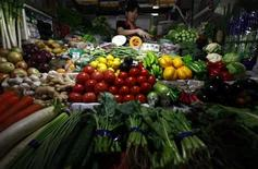 A vegetable seller waits for customers in her stall at a market in central Beijing June 1, 2012. REUTERS/David Gray