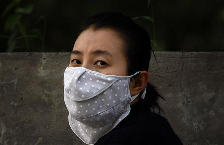 A woman wears a face mask as she walks along a main road in Beijing June 4, 2012. REUTERS/David Gray