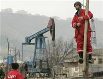 Рабочие на нефтяном промысле в Баку 17 марта 2009. Госнефтекомпания Азербайджана (ГНКАР) до конца 2012 года планирует взять иностранный кредит в $500 миллионов в дополнение к уже имеющемуся кредитному портфелю в объеме свыше $1,6 миллиарда. REUTERS/David Mdzinarishvili