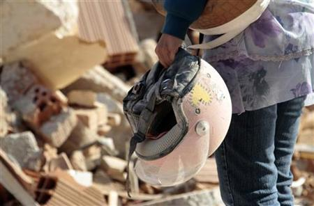 A woman holds a helmet that she found in front of a damaged building in Cavezzo near Modena May 30, 2012. REUTERS/Stefano Rellandini