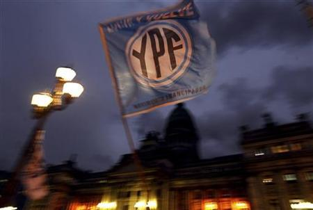 A flag with the YPF logo is waved in front of the Argentine Congress in Buenos Aires, April 25, 2012. REUTERS/Marcos Brindicci