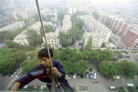 A worker cleans the windows of an apartment block on a haze day, in central Beijing, June 6, 2012. REUTERS/Jason Lee