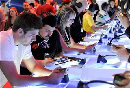 6月5日、ソニー・コンピュータエンタテインメントのハウス社長は、携帯型ゲーム機「プレイステーションVITA」の2012年度の販売台数は1000万台を計画していると明らかに。写真はゲーム見本市「E3」でVITAを手に取る来場者(2012年 ロイター/Gus Ruelas)