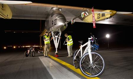 Crew members check the Solar Impulse plane after it landed following a 19-hour flight from Madrid at Rabat's International airport, June 5, 2012. REUTERS/Youssef Boudlal