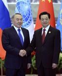 Президент Казахстана Нурсултан Назарбаев и председатель КНР Ху Цзиньтао обмениваются руковопожатием на встрече в Пекине 6 июня 2012. Богатый нефтью Казахстан, испытывающий дефицит мощностей для ее переработки, занял $1,13 миллиарда на модернизацию НПЗ у Китая, развивающего деловую экспансию в Центральной Азии ради доступа к сырью и энергоносителям. REUTERS/Mark Ralston/Pool