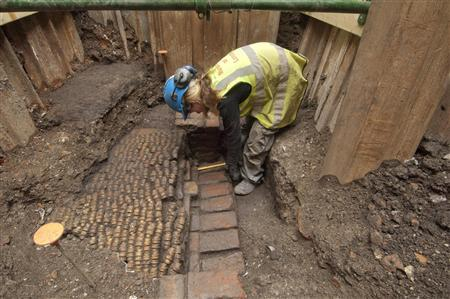 A Museum of London archaeologist measures bricks of the foundation of the Curtain theatre which was unearthed in Shoreditch, east London October 7, 2011. REUTERS/Museum of London Archaeology/handout
