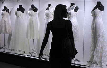 A woman walks by a shop window displaying wedding gowns in Kiev, July 1, 2010. REUTERS/Gleb Garanich