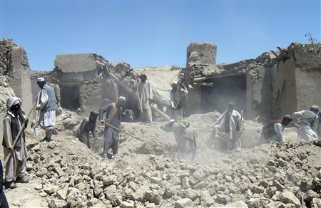 Afghan men search for the bodies of people killed in a NATO airstrike in Logar province June 6, 2012. Officials and villagers in Logar province, about 30 km (17 miles) south of Kabul, said a NATO air strike killed 18 civilians, including women and children, along with six Taliban insurgents. REUTERS/Stringer