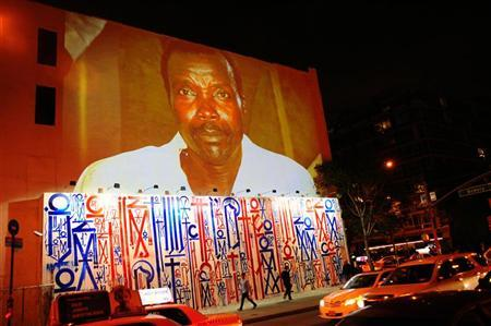 Passersby walk under a projection that is part of the non-profit organization Invisible Children's ''Kony 2012'' viral video campaign, in New York April 20, 2012. REUTERS/Keith Bedford
