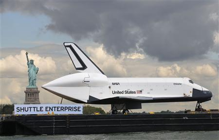 The Space Shuttle Enterprise, passes the Statue of Liberty as it rides on a barge in New York harbor, June 6, 2012. The Space Shuttle Enterprise was being moved up the Hudson River to be placed at the Intrepid Sea, Air and Space Museum. REUTERS/Mike Segar