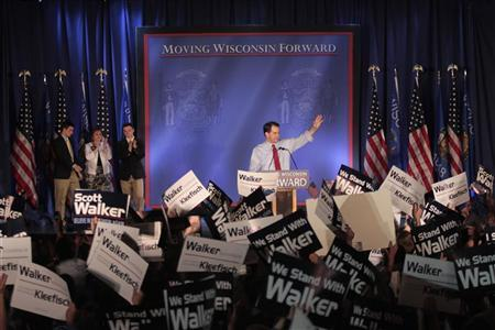 Republican Wisconsin Governor Scott Walker (C) waves as he celebrates his victory in the recall election against Democratic challenger and Milwaukee Mayor Tom Barrett in Waukesha, Wisconsin June 5, 2012. The rematch with Milwaukee's Democratic Mayor Barrett, who Walker defeated in a Republican sweep of the state in 2010, is the end-game of six months of bitter fighting in the Midwestern Rust Belt state over the union restrictions Walker proposed and enacted. REUTERS/Darren Hauck