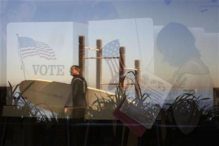 A passing surfer is reflected on the window as voters cast their ballots from inside a beach front polling place in the Los Angeles County lifeguard station in Hermosa Beach, California November 2, 2010. REUTERS/David McNew