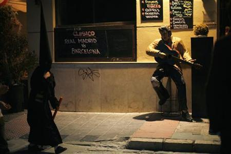 A penitent walks past a statue of Elvis Presley placed outside a bar as he leaves the procession of ''Salesianos'' brotherhood during Holy Week in the An dalusian city of Malaga, southern Spain, April 20, 2011. REUTERS/Jon Nazca