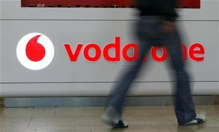 A customer walks past the Vodafone logo in a shopping mall in Prague February 7, 2012. British telecommunication firm Vodafone is expected to post fourth-quarter results on February 9. REUTERS/David W Cerny