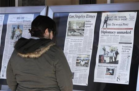 A woman reads U.S. newspapers front pages outside the Newseum in Washington November 29, 2010. REUTERS/Yuri Gripas