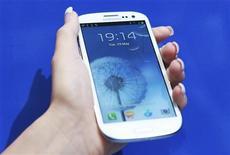 Женщина держит смартфон Samsung Galaxy S III в магазине в Лондоне, 29 мая 2012 года. Samsung Electronics Co заявила, что ее последняя версия смартфона Galaxy S поступит в продажу США, как и планировалось, несмотря на запрос, который Apple подала в американский суд. REUTERS/Olivia Harris