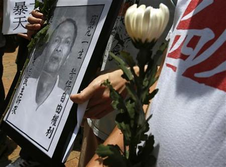 A protester carries a portrait of Chinese dissident Li Wangyang during a demonstration over his death, in Hong Kong June 7, 2012. REUTERS/Bobby Yip