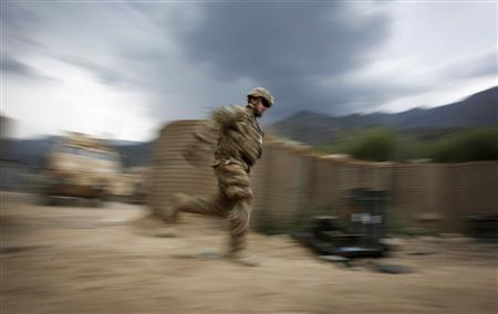 A soldier from the U.S. Army's Alpha Company, 1-12 Infantry, 4th Brigade, 4th Infantry Division, runs across open ground to avoid sniper fire at Combat Outpost Pirtle-King in Afghanistan's Kunar Province June 7, 2012. REUTERS/Tim Wimborne