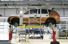 Workers screw on the wheel section of a Cayenne car at the final production unit at the Porsche plant in Leipzig, in this June 2, 2009 file photo. REUTERS/Tobias Schwarz/Files