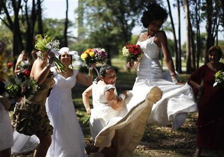 Women in wedding gowns jump during the ''Parade of Brides'' in Sao Paulo October 23, 2011. REUTERS/Nacho Doce