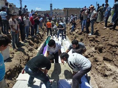 People gather at a mass burial for the victims purportedly killed during an artillery barrage from Syrian forces in Houla in this handout image dated May 26, 2012. REUTERS/Shaam News Network/Handout