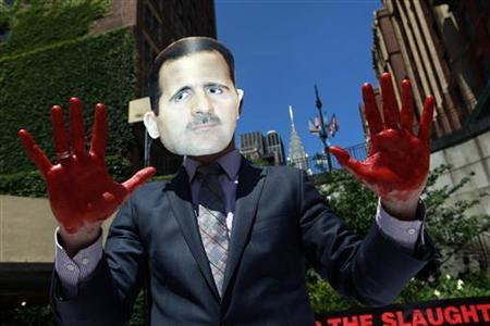 A protester from the activist organization Avaaz wearing a mask of Syrian President Bashar al-Assad holds up hands covered in red paint during a demonstration outside the U.N. headquarters in New York June 7, 2012. REUTERS/Allison Joyce