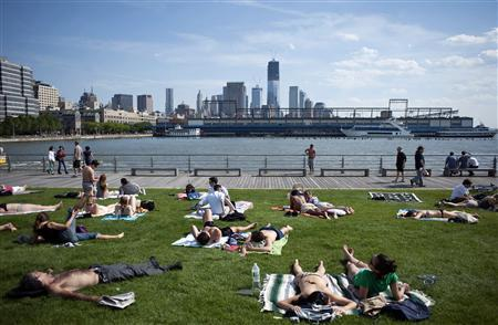 People lay out on the grass in the sun along a pier facing the Hudson River in New York in this file photo taken May 13, 2012. So far, 2012 has been the warmest year the United States has ever seen, with the warmest spring and the second-warmest May since record-keeping began in 1895, the U.S. National Oceanic and Atmospheric Administration reported on Thursday. REUTERS/Keith Bedford/Files