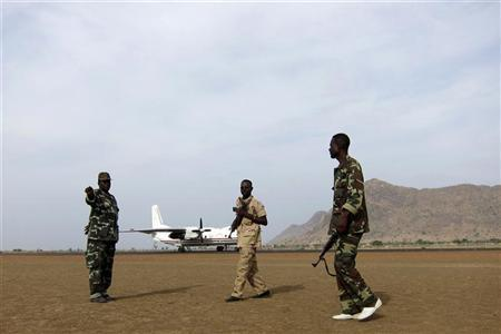 Armed soldiers stand guard near an aircraft at Talodi in South Kordofan, about 50 km from Sudan's ill-defined border with South Sudan, April 12, 2012. REUTERS/Alexander Dziadosz