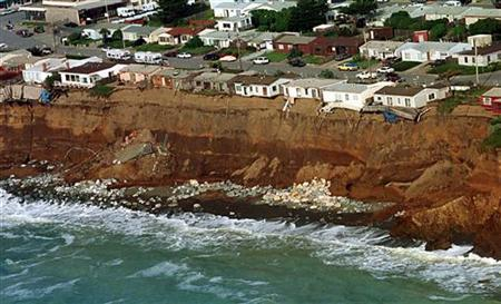 Homes which are sliding in to the sea in Pacifica, California are seen from the air, March 4. 1998. REUTERS/Sean Ramsey
